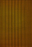 Black hole grid with yellow backlight. Black hole grid with many small rectangular holes and yellow orange backlight Royalty Free Stock Image