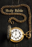 Black Holy Bible & Pocket Watch. A pocket watch on the cover of the Holy Bible Stock Photos