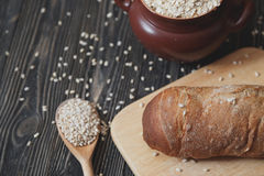 Black homemade bread and its ingredients on rustic table. Royalty Free Stock Photo