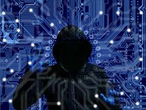 Black hooded hacker on a blue circuit background cybersecurity I Royalty Free Stock Image