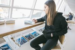 Black hoodie girl in light whitw cafe. Lovely relaxed mood. Time for hobby. royalty free stock photography