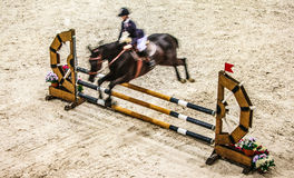 Black horse with rider jumping over obstacle. Riding competition. Royalty Free Stock Image