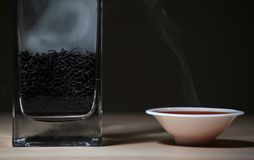 Black Hot Chinese tea cup smoke wooden table dark background nobody. Studio royalty free stock photo