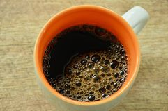 Black hot coffee with bubble floating in cup on table royalty free stock photos