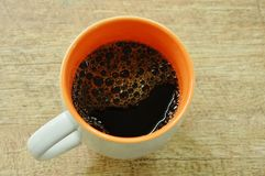 Black hot coffee with bubble floating in cup on table royalty free stock photography