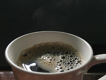 Black hot coffee with bubbles and foam in cup close up on wooden table stock images