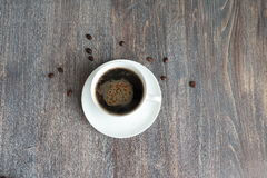 Black hot coffee in a white cup on a wooden table. Special light. Royalty Free Stock Images