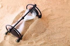Black hourglass. On the beach sand Stock Image