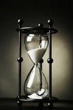 Black hourglass on a black background Royalty Free Stock Photos