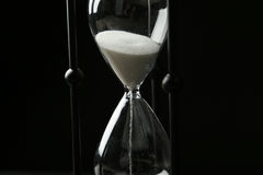 Black hourglass on the black background Royalty Free Stock Image