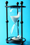 Black hourglass on the blue background Stock Photo