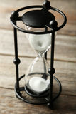 Black hourglass on a grey wooden background Royalty Free Stock Images