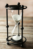 Black hourglass on the grey wooden background Royalty Free Stock Images