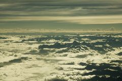 A Black huge mountain valley protruding from the white clouds. mountains above the clouds. mountain view from a great height. Black huge mountain valley stock photos