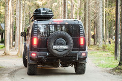 Black Hummer H2 vehicle goes on dirty country road Stock Image