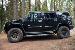 Black Hummer H2 vehicle stands on dirty country road Royalty Free Stock Photos
