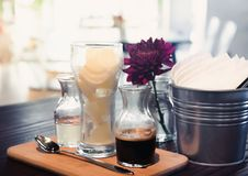 Black iced coffee latte serve with frozen milk. And glass of liquid sugar on cafe. Coffee latte were in glass jar stock photos