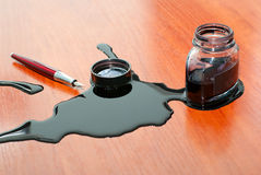 Black ink spill near red pen on table stock image