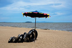Black inner tube under umbrella at sea Royalty Free Stock Photography