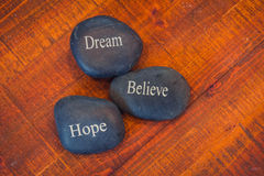 Black inspirational pebble stones with the words Dream, Believe. And Hope on wooden background royalty free stock photography