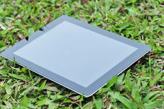 Black ipad on green grass Stock Images