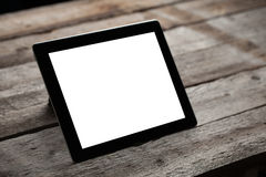 Black ipad on old wood table. Background royalty free stock photography