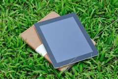 Black ipad and protect case. New black ipad4 and protect case on green grass royalty free stock image
