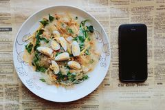 Black Iphone 5 Near Plate of Pasta Dish Stock Photo