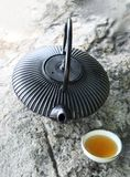 Black iron asian teapot with cup of tea on rock Stock Photo