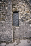 Black iron door with handle in ancient stone wall Royalty Free Stock Image