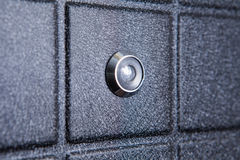 Black iron door of squares with silver peephole Stock Image