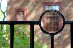 Black iron fence in front of red brick building Royalty Free Stock Photography
