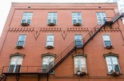 Black Iron Fire Escape Past Windows of Brick Building Stock Image
