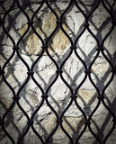Black iron grid on a stone wall stock photography