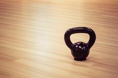 Black iron kettlebell weight on wooden floor Stock Photography