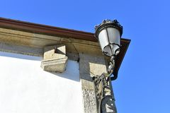 Black iron light and sundial on a stone wall with blue sky. Ponte Maceira, La Coruna Province, Spain. royalty free stock photos