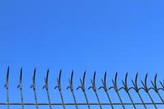 Black iron sharp fence on blue sky background Royalty Free Stock Images