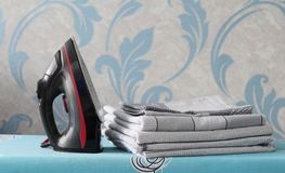 A black iron stands on the ironing board. Near a pile of bed linen stock images