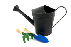 Black iron watering can with shovel and rake. Isolated on white background royalty free stock photos