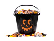 Black Jack o Lantern candy collector with candy pile over white. Black Halloween Jack o Lantern candy collector with scattered candy over a white background Stock Photo