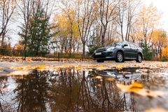 Black SUV on autumn road in rainy day. Black japanese SUV on autumn road in rainy day Royalty Free Stock Photography