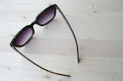 Black jeweled sunglasses on white wood Royalty Free Stock Photos