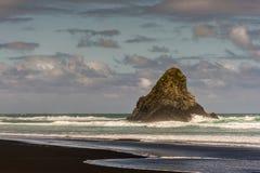 Black Karekare Beach with the Watchman Rock. Auckland, New Zealand - March 2, 2017: Black sand Karakare Beach under blue cloudy sky with, Te Kaka Whakaara Rock Stock Image