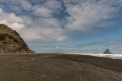 Black Karekare Beach with the Watchman Rock in distance. Auckland, New Zealand - March 2, 2017: Wide shot of black sand Karakare Beach under blue cloudy sky Stock Photography