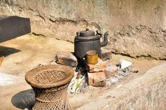 Black kettle on bricks to boil water and make tea in a village in the morning for house hold use with a Traditional indian seat.. Black kettle on bricks to royalty free stock image