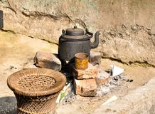 Black kettle on bricks to boil water and make tea in a village in the morning for house hold use with a Traditional indian seat.. Black kettle on bricks to stock images