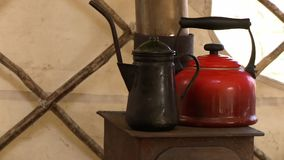 A teapot and kettle on a rustic stove. A black kettle and a red teapot on top of an old rustic stove inside a tent stock video