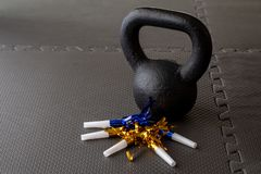 Black kettlebell on a black gym floor with blue and gold noisemakers stock photo