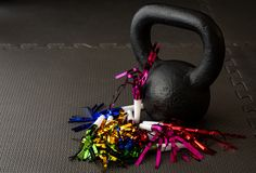 Black kettlebell on a black gym floor with blue, green, red, pink and gold noisemakers stock photos