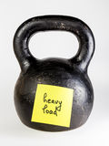 Black kettlebell with label heavy load Royalty Free Stock Images